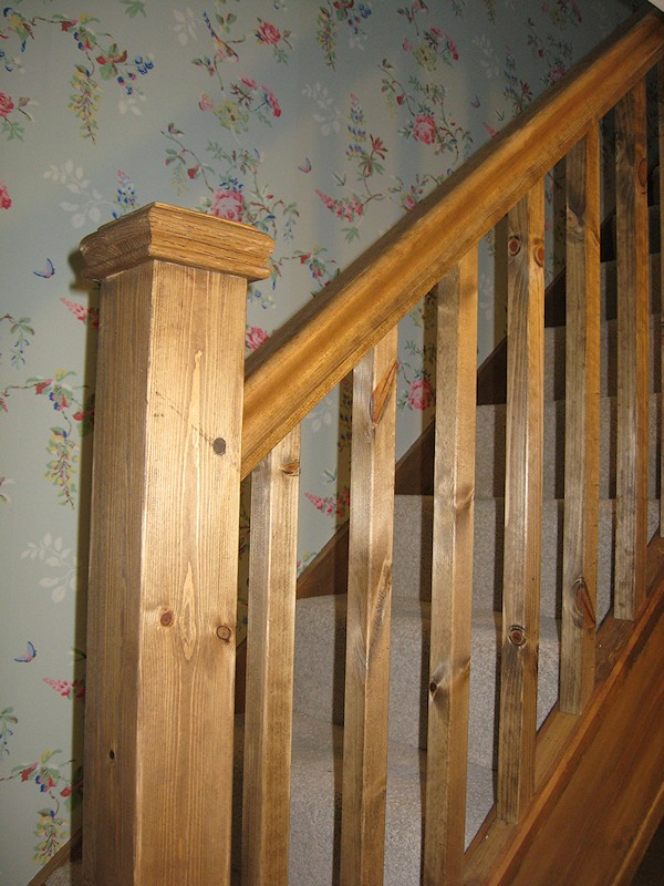 A single turn winder staircase constructed in softwood and finished in dark wood stain.