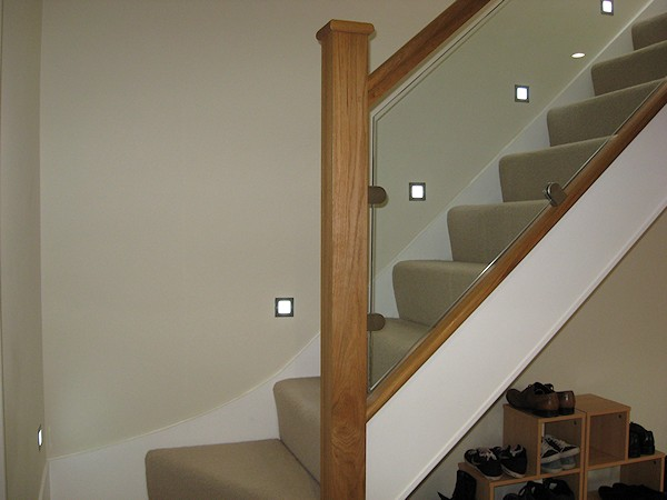 This staircase has an ultra modern feel with glass balustrade and lighting mounted above the wall string.