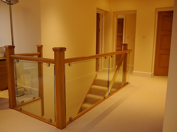 Another oak straight flight starcase with glass balustrade.
