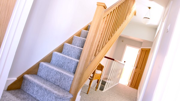 Oak staircase with our std profile handrail, square 32mm spindles and pyramid newel caps.